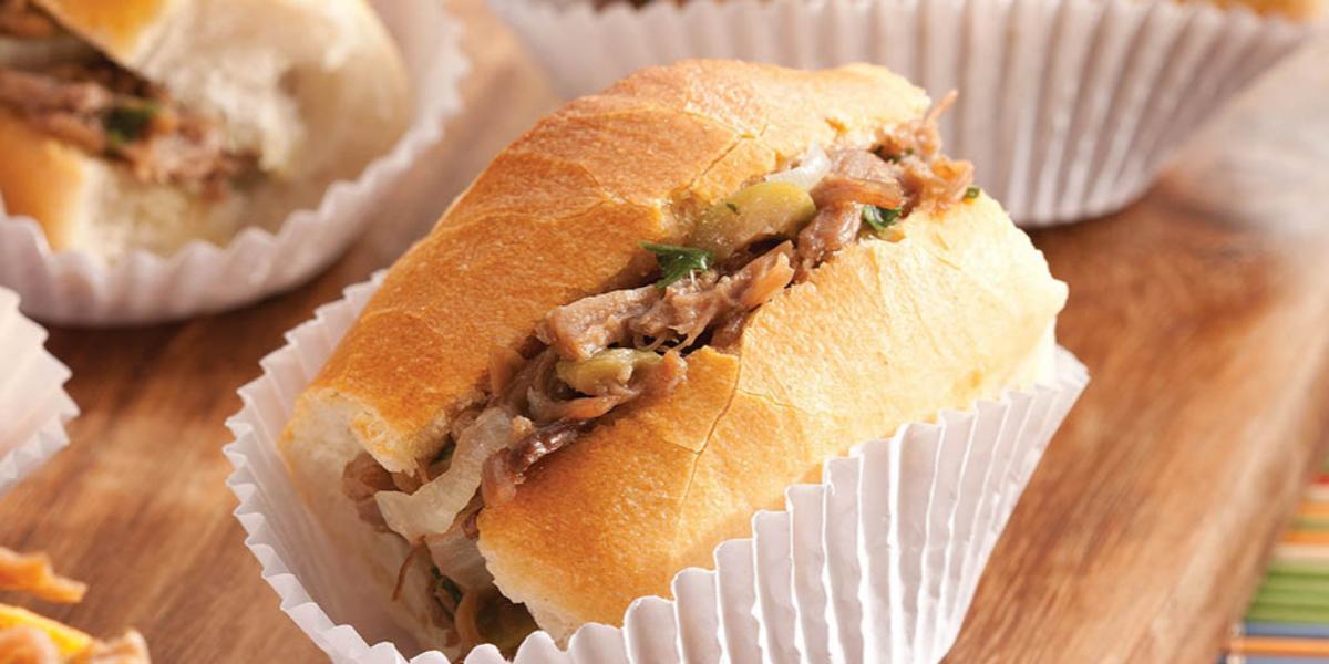 Fotografia em tons de marrom e amarelo tábua de madeira com sanduíches de mini pão francês recheados com carne louca dentro de forminhas de papel.