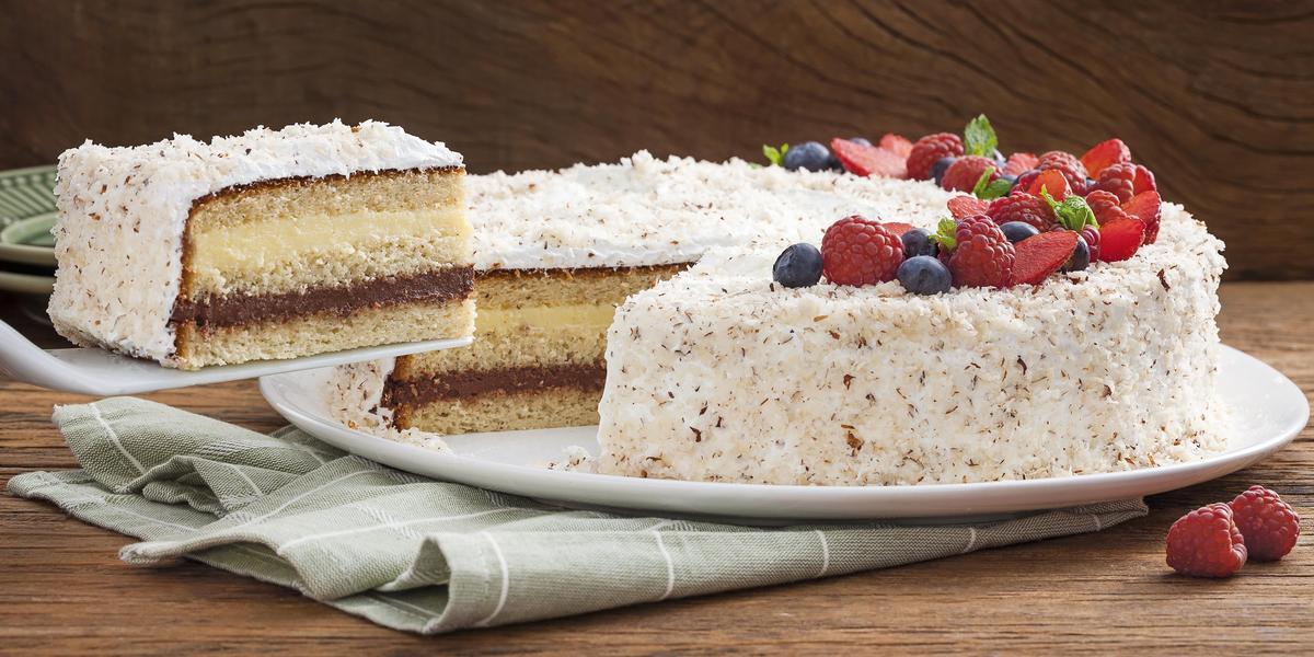 Fotografia em tons de marrom, verde e branco de uma bancada de madeira escura com um paninho verde, sobre ele um prato branco redondo com um bolo recheado e coberto com frutas vermelhas.