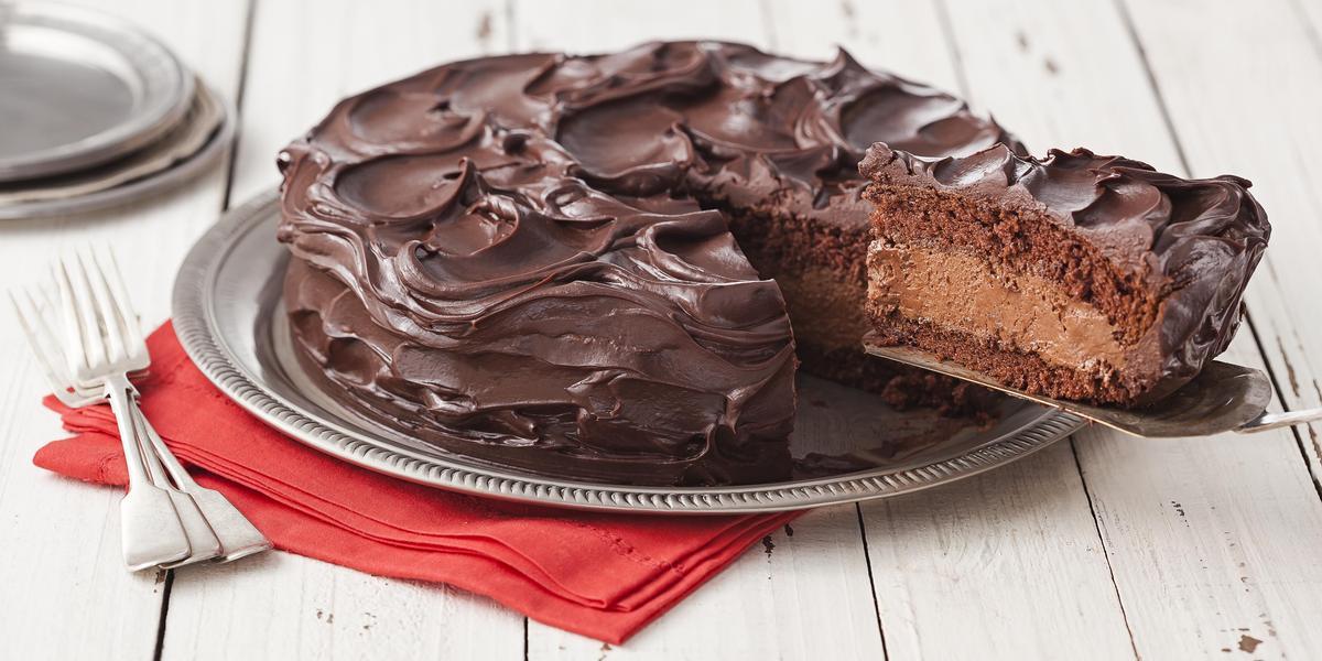 Fotografia em tons de branco e marrom de uma bancada de madeira, um paninho vermelho, um prato redondo prateado, dois garfos prateados e um bolo de chocolate com uma fatia sendo retirada, mostrando o recheio de mousse.