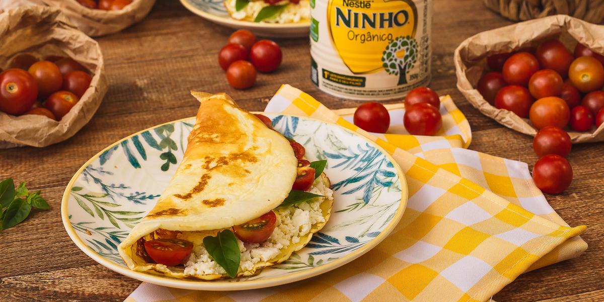 Fotografia em tons de amarelo e vermelho de uma bancada de madeira com um pano xadrez amarelo e branco, uma prato com uma crepioca recheada de queijo e tomate. Ao fundo tomates-cereja, uma lata de NINHO e ovos.