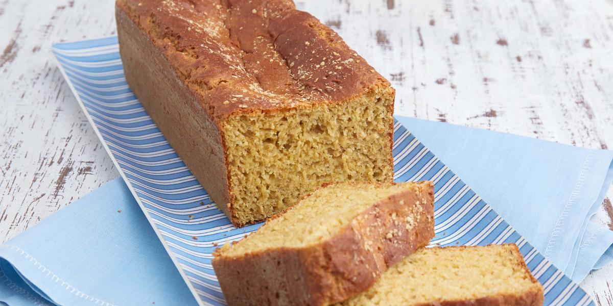 fotografia em tons de azul e bege de uma mesa vista de cima, contém um pano azul com um prato azul e por cima um pão com duas fatias na frente