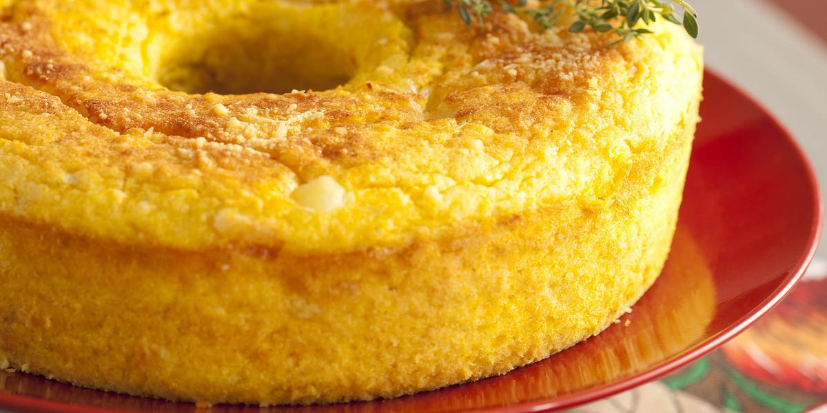 Fotografia em tons de cinza, vermelho e amarelo, de uma bancada cinza com um paninho estampado florido e um suporte de bolo vermelho, sobre ele um bolo de milho salgado e um ramo de orégano fresco.