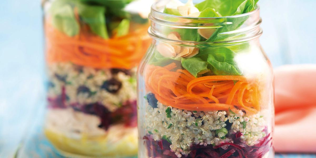 Fotografia em tons de azul em uma bancada de madeira azul, dois potinhos de vidro com a salada de quinoa, beterraba, cenoura e agrião dentro deles. Ao lado, um paninho rosa e dois garfos.