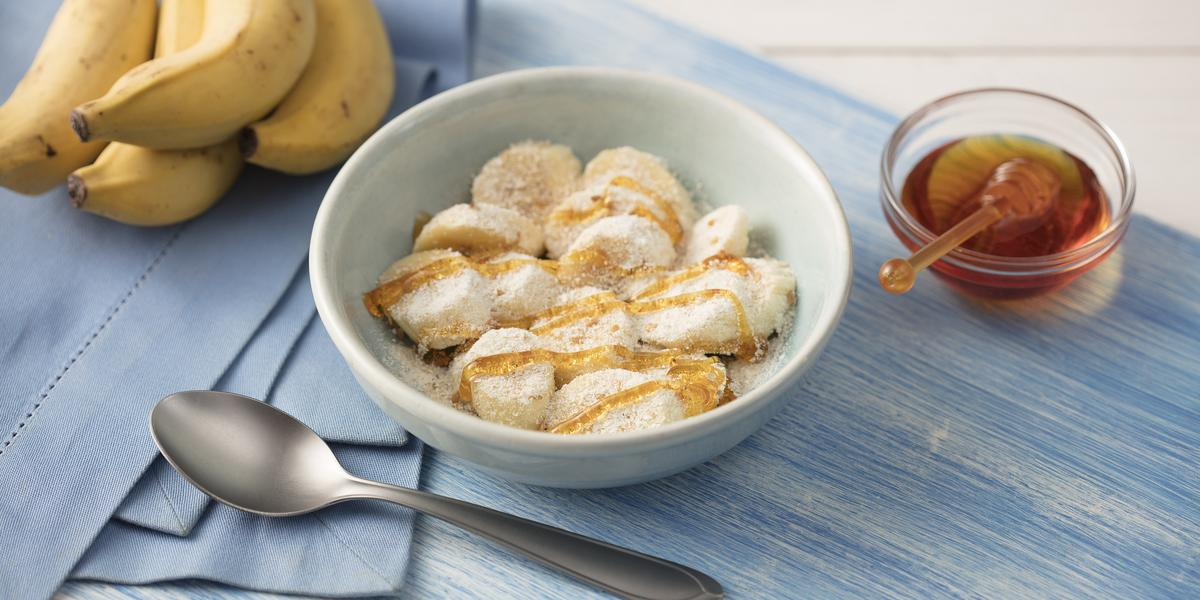 Fotografia em tons de azul em uma mesa de madeira clara com um paninho azul ao lado, um prato branco redondo fundo com as rodelas de banana cobertas com mel, aveia, leite em pó e linhaça. Ao lado, um cacho de bananas e um potinho com mel.