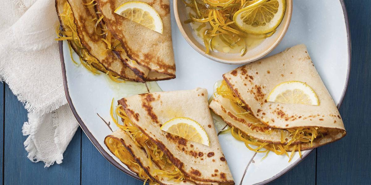 Fotografia em tons de branco, azul, amarelo, ao centro um prato branco com crepes recheados com raspas de laranja e decorados com fatias limão, ao lado potinho com raspas de laranja e limão, guardanapo branco, tudo sobre bancada azul.