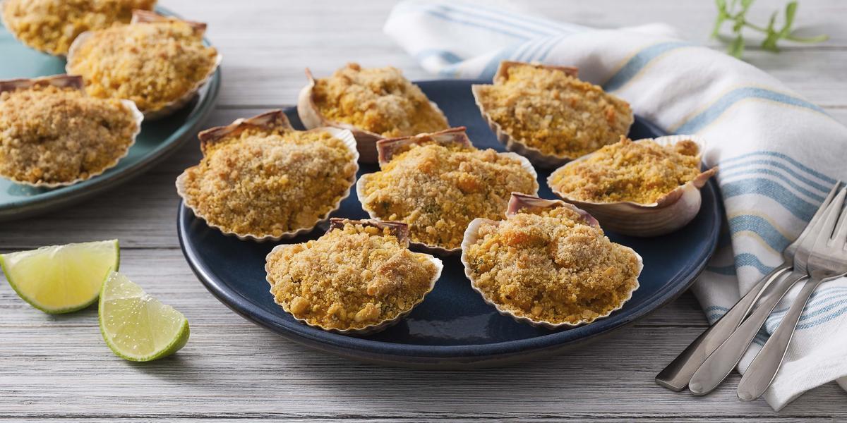 bancada de madeira em tons cinza, casquinhas de Siri em cima de um prato azul, ao lado fatias de limão e do outro um pano listrado em azul e talheres por cima do pano.
